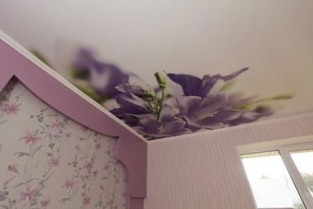 Матовый натяжной потолок в интерьере зала с фото цветов, оформленный в фиолетово-белых тонах