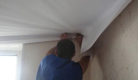Накидывание ткани за багет при монтаже натяжного потолка