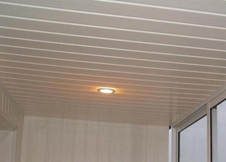 На фото узкая кухня за счет правильного использования полос потолка визуально расширилась