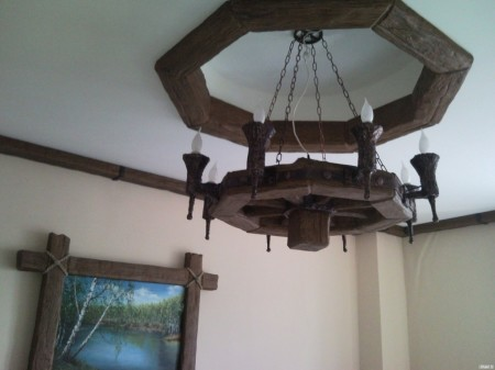 Балки декоративные в центре помещения и эксклюзивная люстра – гармоничное сочетание