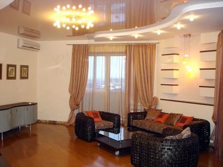 Натяжной потолок гостиной в центре украшен люстрой, а точечная подсветка разбросана по периферии равномерно освещает помещение