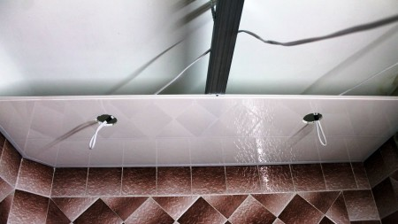 Заключительный этап монтажа пластикового потолочного профиля к каркасу, выполненного из любого материала