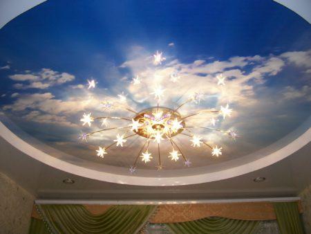 Фото натяжного потолка с фотопечатью в виде облаков и центральной люстрой