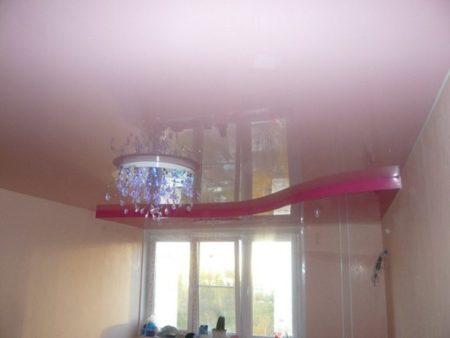 Глянцевый двухуровневый потолок за счет ступени выдвигает окно на первый план, и в небольшой комнате стало казаться просторнее