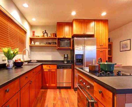 На этом фото дизайн кухни с классическим деревянным гарнитуром и сатиновый натяжной потолок