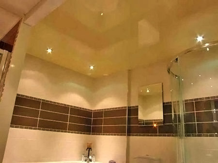 Гармоничный дизайн ванной комнате: глянцевый потолок в одном тоне с отделкой стен