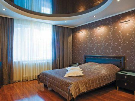 Фото уютного и лаконичного интерьера спальни с матовой поверхностью круглого зеркала, расположенного на потолке над кроватью