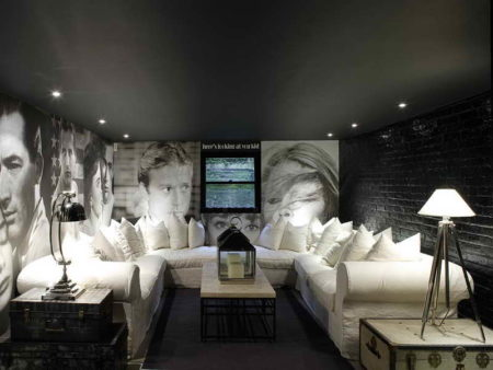 Уютная небольшая гостиная с фото на стенах и необычным потолком