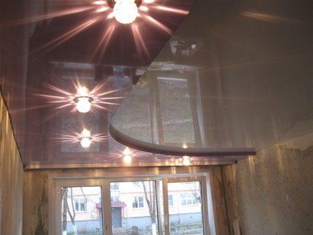 Если в многоуровневой конструкции использовать еще и полотна разного цвета, то потолок не только увеличит объем зала, но и отчетливо разделит помещение на две зоны