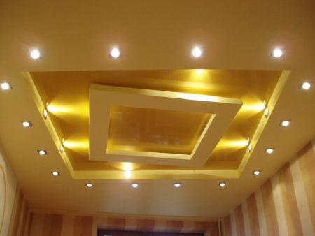 Фото многоуровневого натяжного потолка с нестандартным центровым элементом декора и точечными светильниками