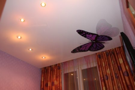 Внешний вид светло-бежевого натяжного потолка с фотопечатью в виде бабочки