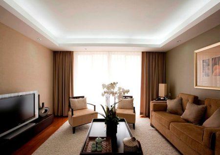 Натяжной потолок с обрамлением в виде прямого короба из гипсокартона – типичный дизайн гостиной в городской квартире