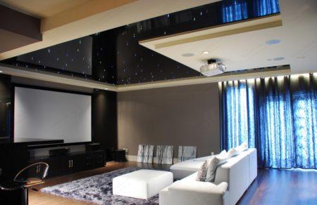 Привлекательный гармоничный дизайн гостиной с темным глянцевым потолком по типу звездного неба